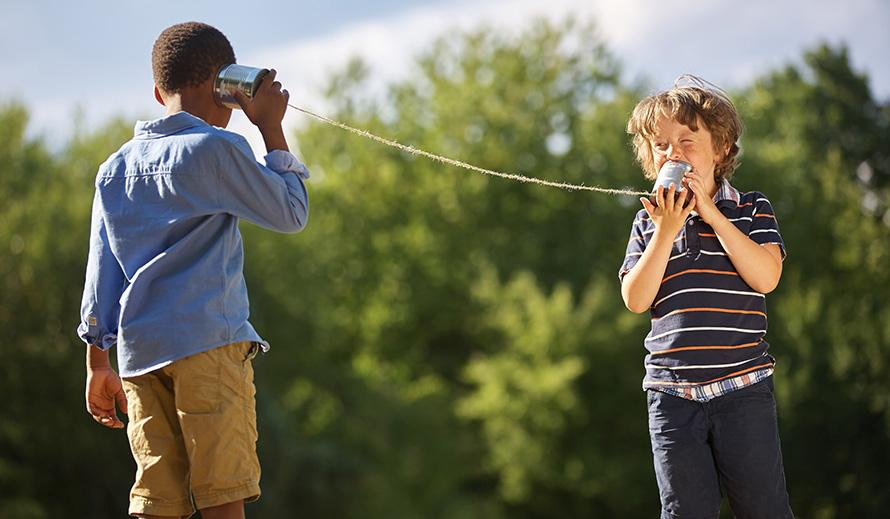Boys communicating using two cans tied with string.