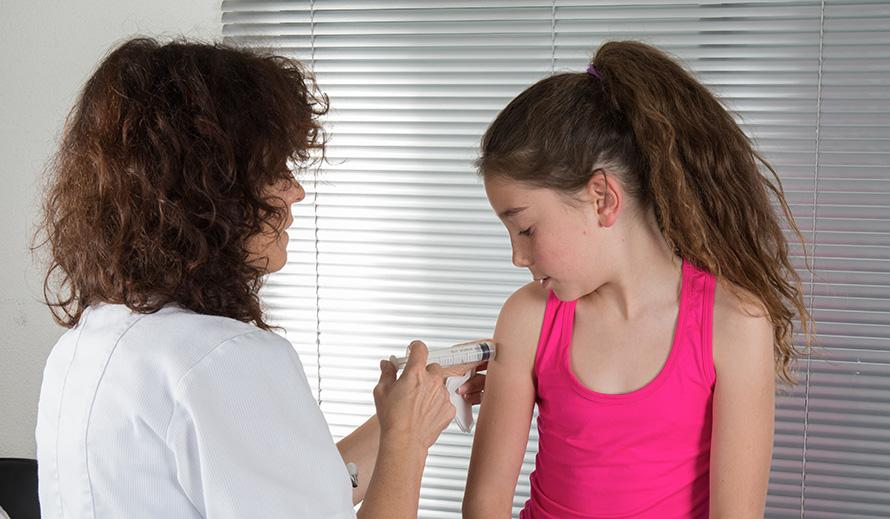 Girl in a clinical setting getting a vaccine.