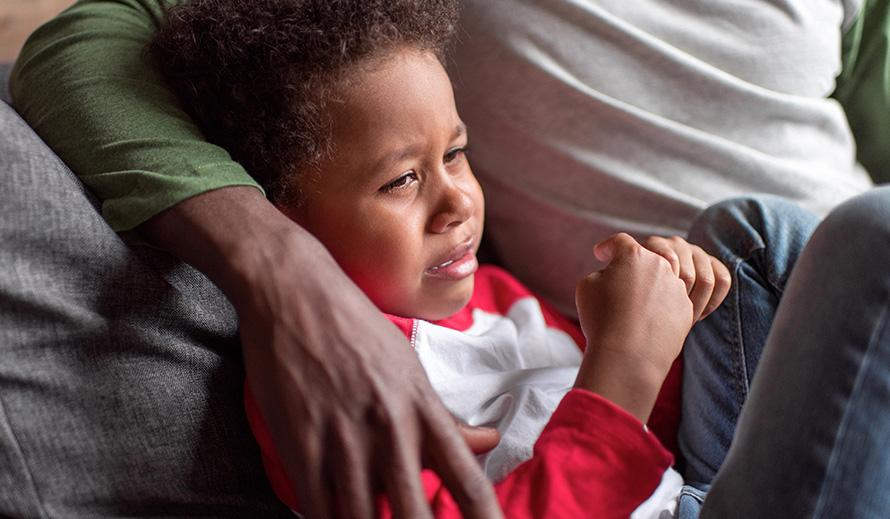 A distressed young African-American boy curled up on the couch being comforted by his father.