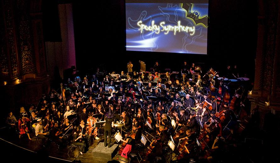 "A costumed symphony orchestra performing a concert while cartoon ghosts, bats and the words ""Spooky Symphony"" are projected onto a big screen above them."