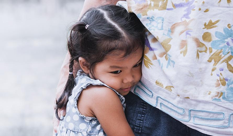 A little Hispanic girl, crying and standing next to her mother with her arms wrapped around her waist.