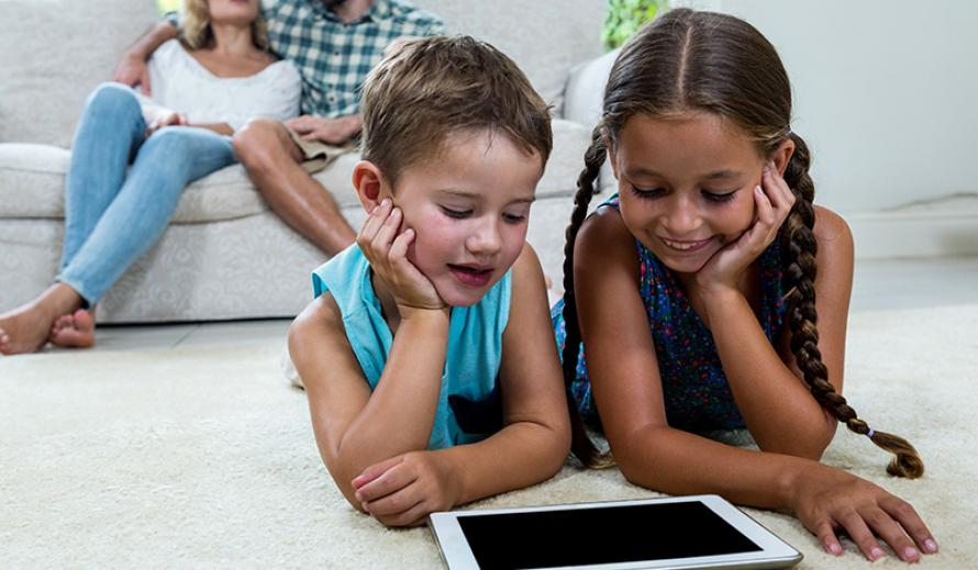 Two young girls spend some screen time at home while parents look on.