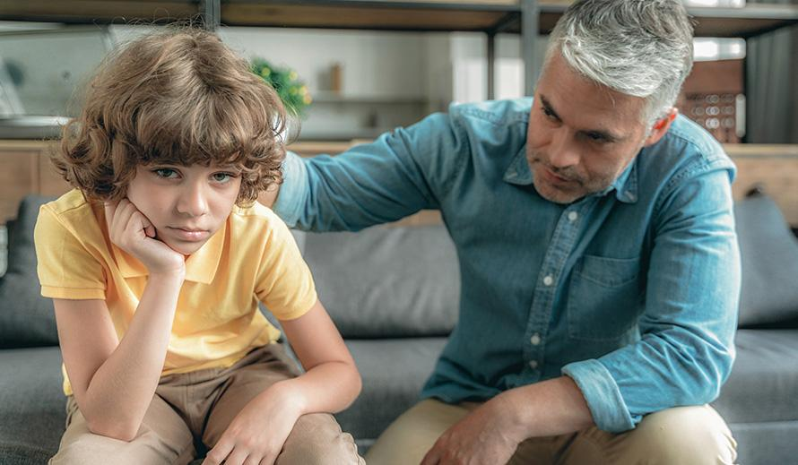 Father comforts boy in emotional distress.