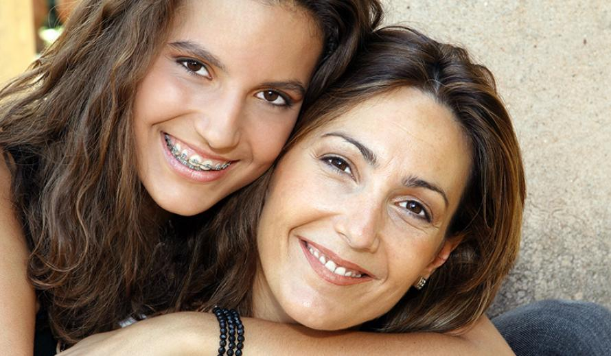 Teen daughter with arm around mother, both smiling