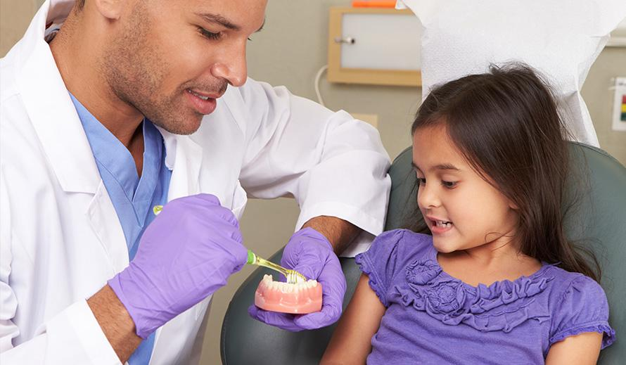Dentist showing a little girl how to brush her teeth