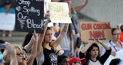 Teens holding signs at gun control rally