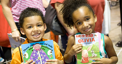 Smiling boy and girl, each holding a book.