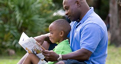 Padre leyendo un libro a su hijo en el parque