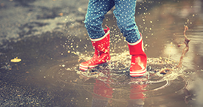 Child's rubber boots-clad legs jumping in a puddle