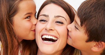 Happy mom being kissed on either cheek by her children