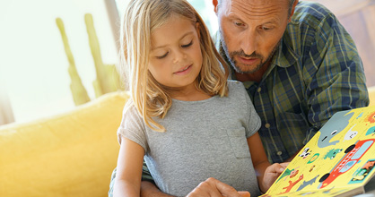 Father and daughter reading together at home.
