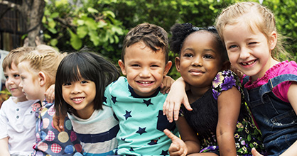 Smiling group of multiracial children, hugging.