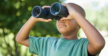 Little boy looking through binoculars.