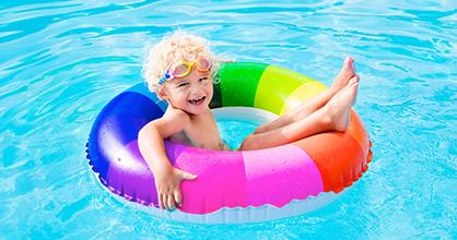 Happy little boy on a rainbow-striped floatie in a swimming pool.
