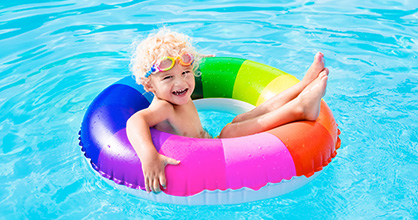 Happy little boy on a rainbow-striped floatie in a swimming pool.