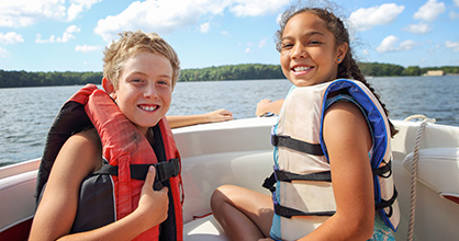 Happy girl and boy wearing life jackets on a boat.