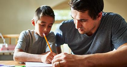 A father tutors his son.