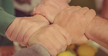 Cuatro manos entrelazadas en las muñecas.