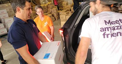 El presidente y director ejecutivo de Children's Trust, James Haj, carga libros durante un evento de distribución en el verano.
