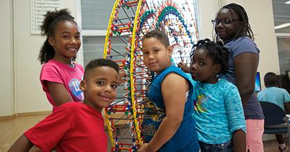 Los niños afroamericanos construyen una mini noria durante el campamento de verano.