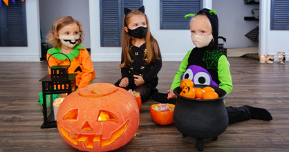 Young girls celebrate Halloween in a safe way inside the home during Halloween.