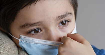 A Hispanic boy looks despondent during the coronavirus pandemic.