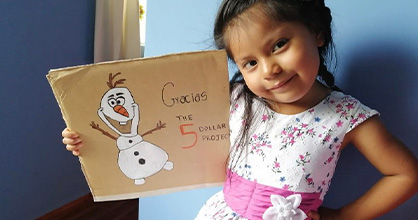 A young girl shows a sign of thanks to the Five Dollar Project.