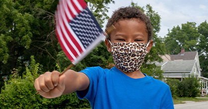 A young boy waves an American flag with a mask on.