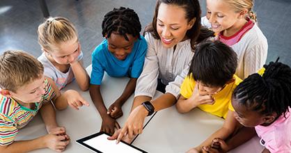 Una maestra de aprendizaje temprano habla con un grupo de niños que la rodean en una mesa.