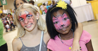 Two smiling young girls with painted faces, one a demon and one a cat, at the Family Expo.