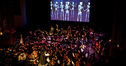 Orchestra on stage beneath a giant screen projecting dancing skeletons.