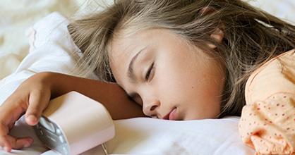Little girl asleep in bed, clutching an alarm clock.