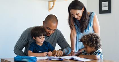 Una familia diversa se sienta alrededor de una mesa leyendo.