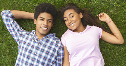 A teenage boy and teenage girl enjoy laying in the grass.